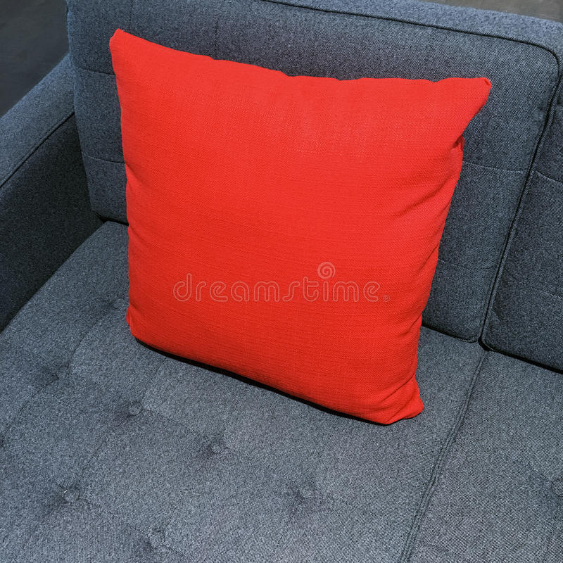 Vibrant red cushion decorating gray sofa. Modern style furniture stock photography