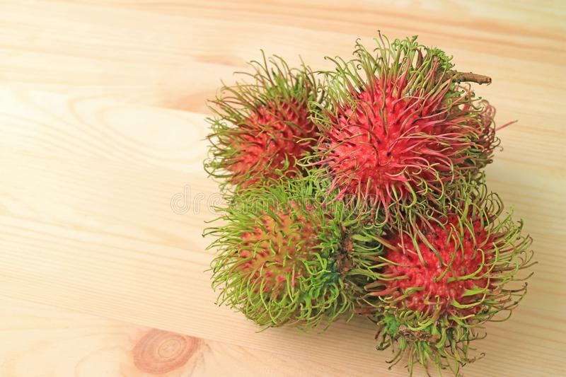 Vibrant Red and Green Fresh Ripe Rambutan Fruits Isolated on Wooden Table stock image