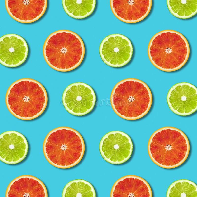 Vibrant red orange and green lime lemon slices pattern on turquoise background. Vibrant red orange and green lime lemon slices pattern on turquoise color stock photos