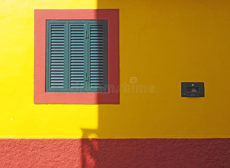 Vibrant red and yellow colorful house wall with a green wooden shutter in a square frame in bright sunlight and shadow royalty free stock photography