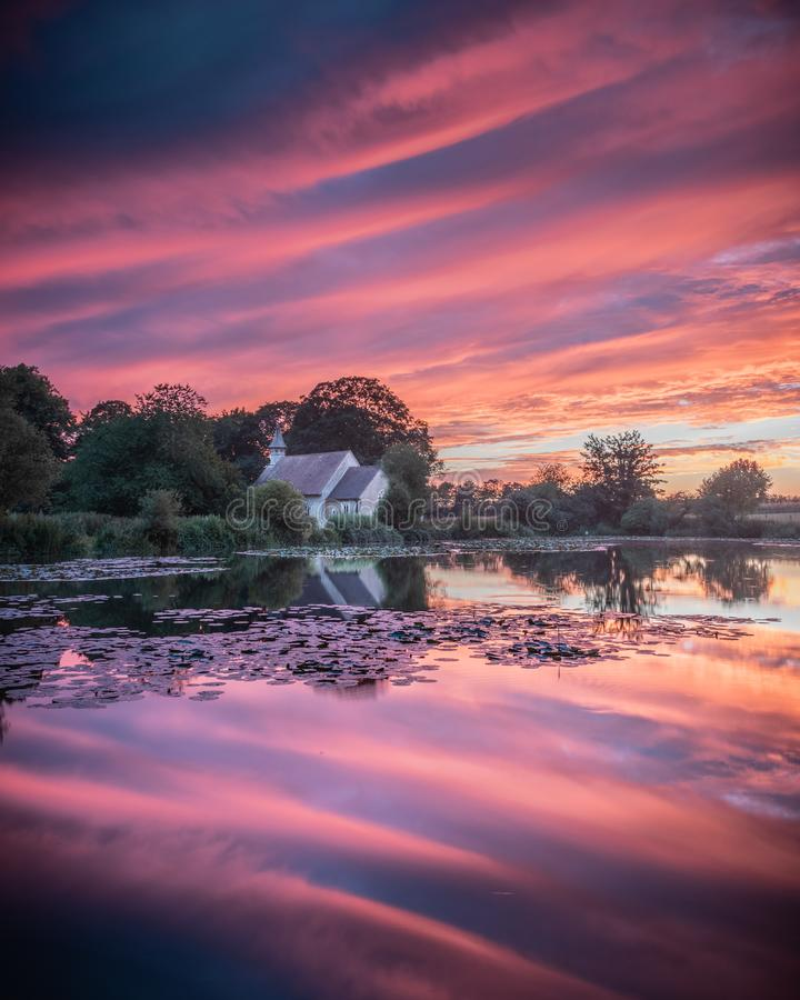 A vibrant sunset reflecting on a lake with a church across the water. A vibrant sunset reflecting on a lake with an old English church across the water royalty free stock image