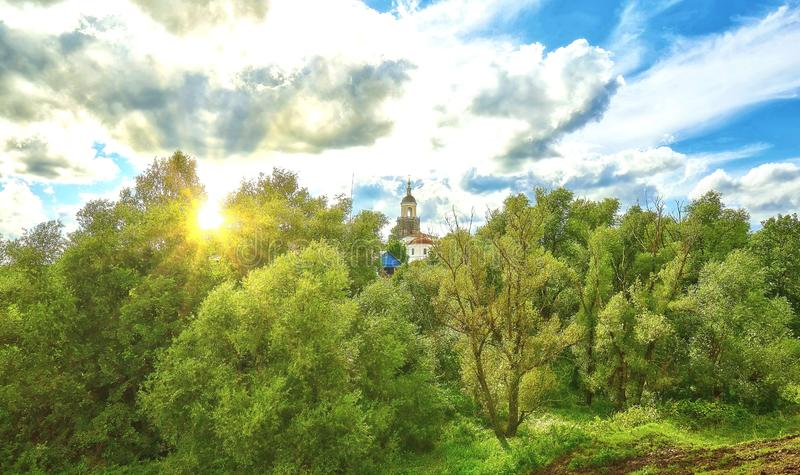 Vibrant view of country side near Vladimir, Russia, with an orth. Odox church with golden cupola surrounded by green trees under summer cloudy sky royalty free stock photos
