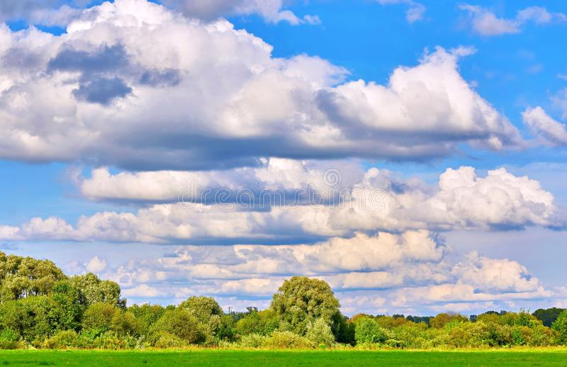 Vibrant wide angle view of a summer countryside landscape and blue cloudy sky stock image
