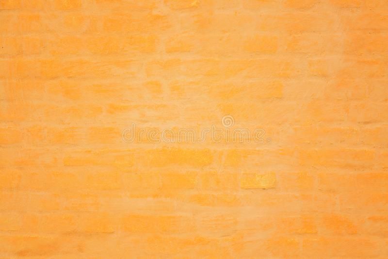 Vibrant yellow or orange brick wall texture background. Abstract architecture detail background stock photography