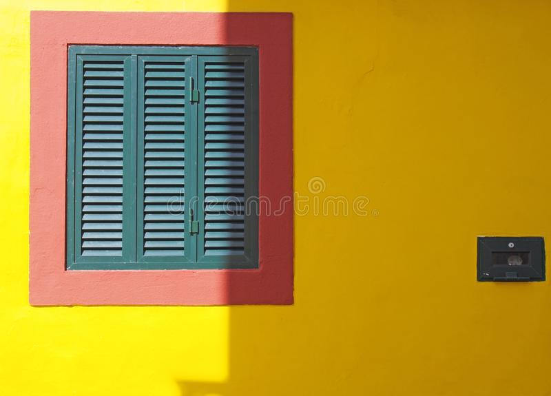 A vibrant yellow wall with red frame and green closed shuttered window typical Portuguese colors in bright sunlight and shade with. Space for copy stock photos