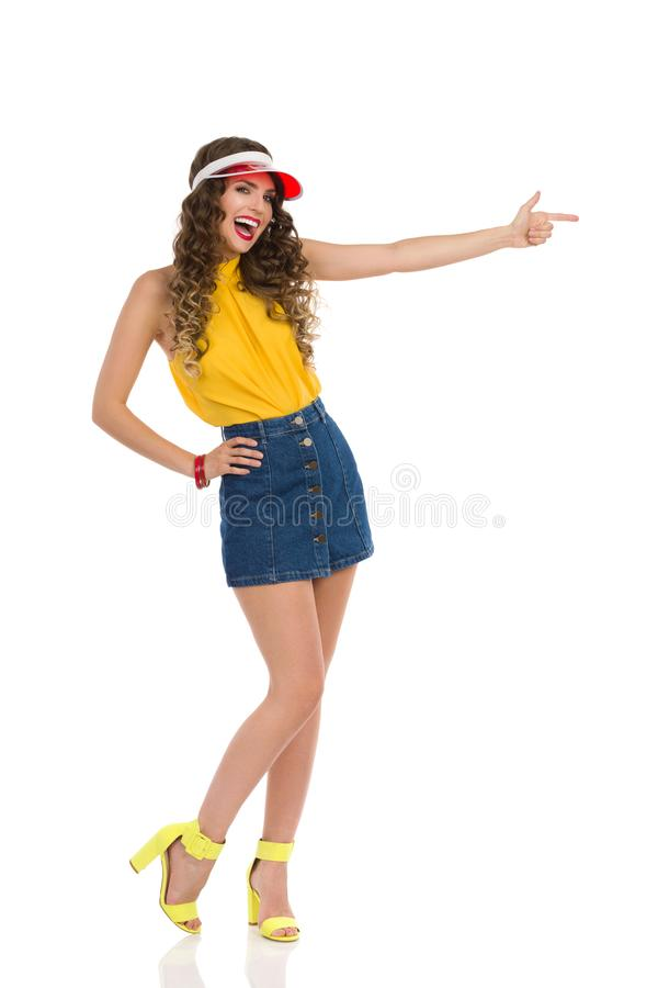 Vibrant Young Woman In Jeans Mini Skirt And High Heels Is Pointing And Laughing. Beautiful young woman in jeans mini skirt, yellow top and high heels is pointing royalty free stock images