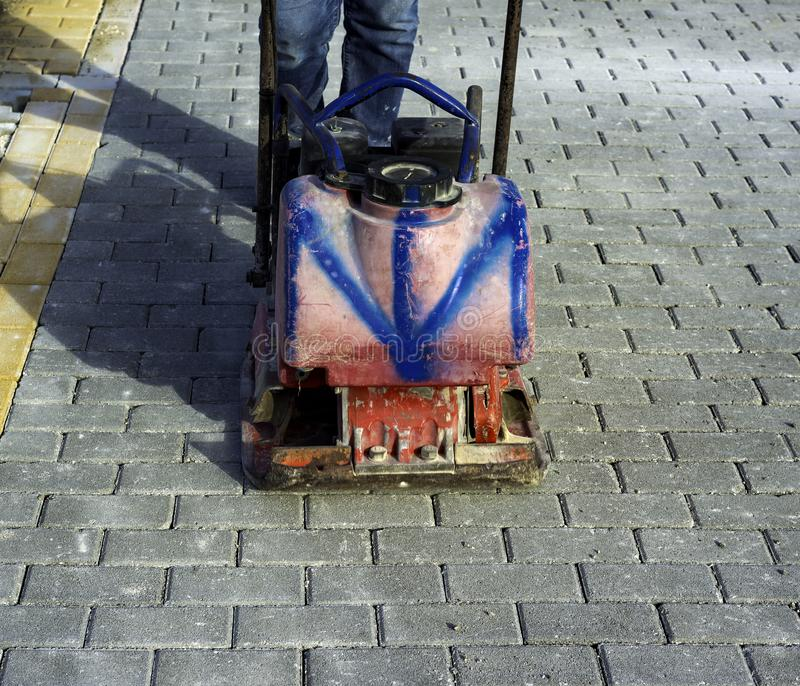 Vibrator with rubber plate for compacting paving. With interlocking blocks stock image