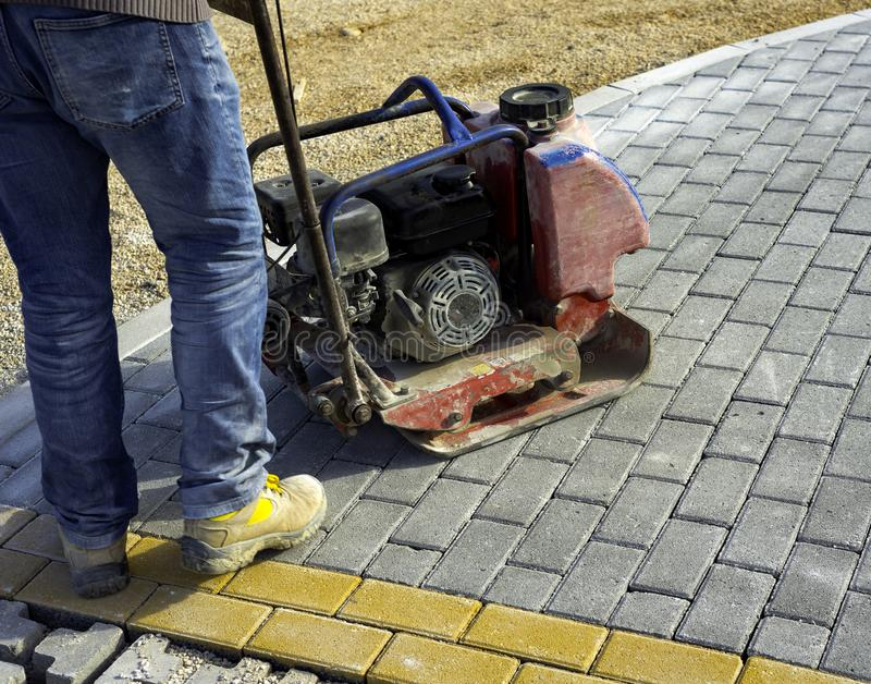 Vibrator with rubber plate for compacting paving. With interlocking blocks royalty free stock photography