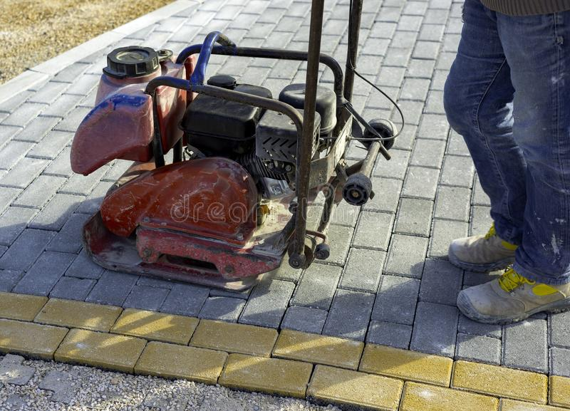 Vibrator with rubber plate for compacting paving. With interlocking blocks stock photos