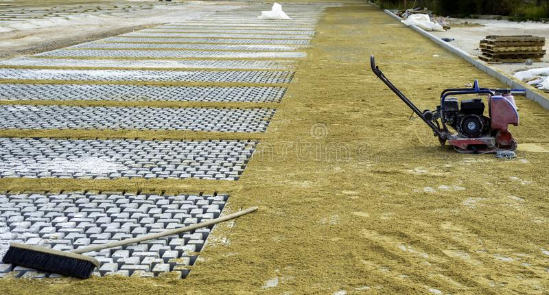 Vibrator with rubber plate for compacting paving. With interlocking blocks stock images