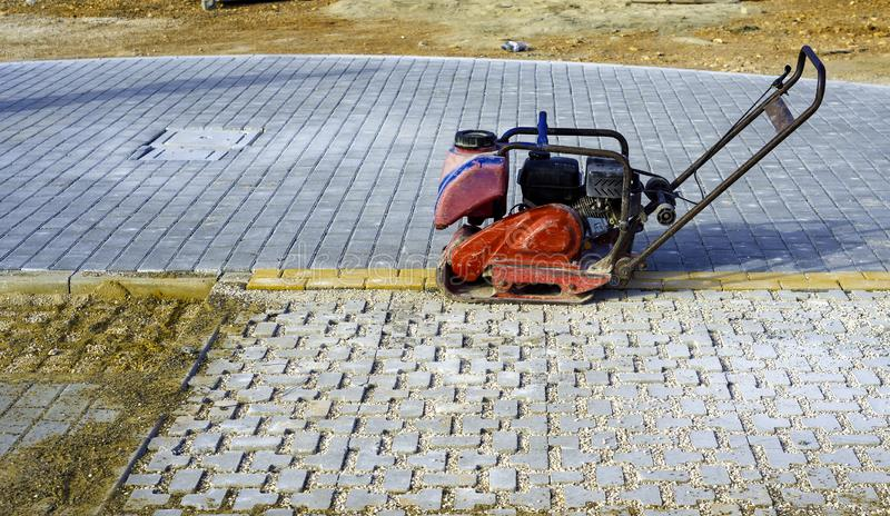 Vibrator with rubber plate for compacting paving. With interlocking blocks royalty free stock images