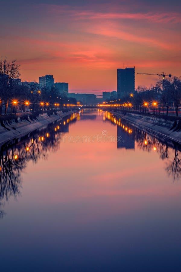 Vibrerande cityscapeskottotta för soluppgång i Bucharest med en flod i förgrunden royaltyfria foton