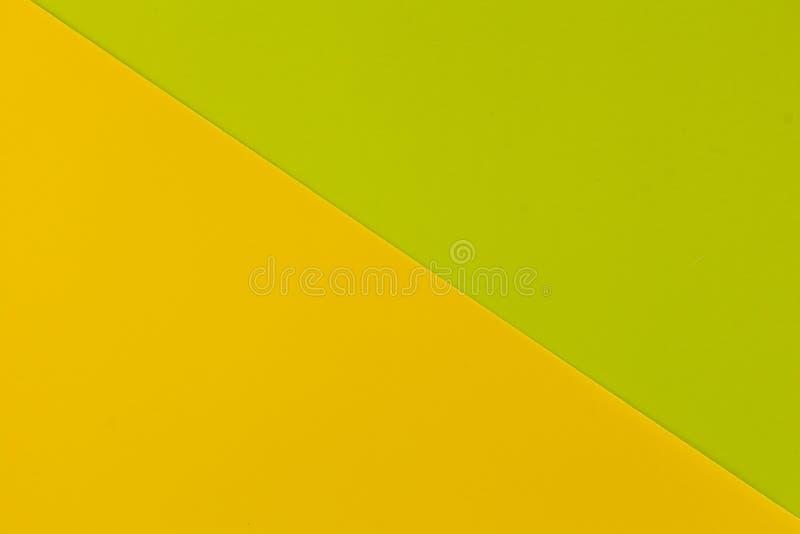 Vibrerande gult och limefrukt färgade plast- yttersidor som diagonalt fogades ihop, bakgrund royaltyfri fotografi