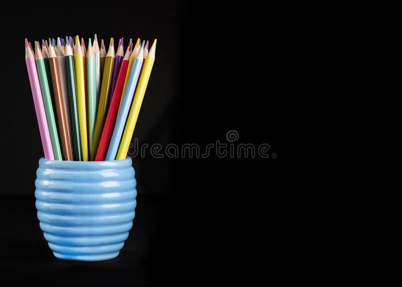 vibrerande kulöra blyertspennor på en tillbringare på ett svart bakgrundsskott för kopieringsutrymme och text över lägger royaltyfri bild