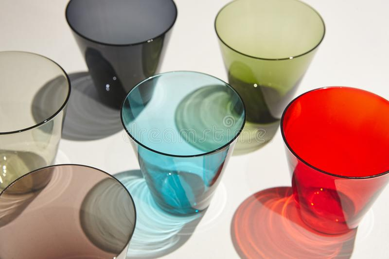 Vibrerande kulöra crystal exponeringsglas på en vit bakgrund crockery royaltyfri fotografi