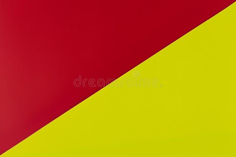 Vibrerande rött och limefrukt färgade plast- yttersidor som diagonalt fogades ihop, bakgrund arkivbild