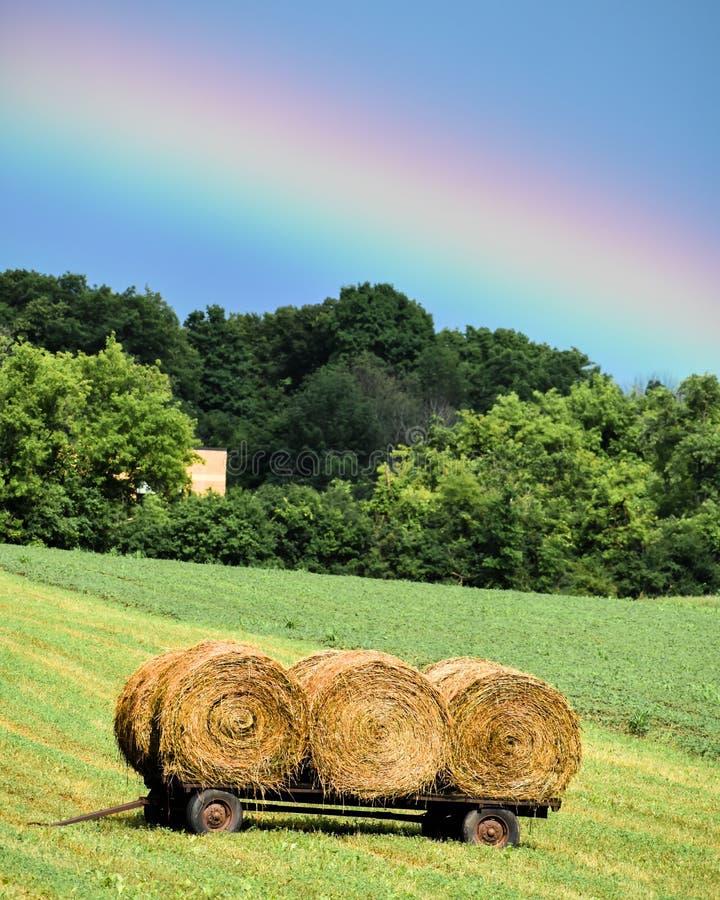 Vibrerande regnbåge över tre rullande höstackar arkivbilder