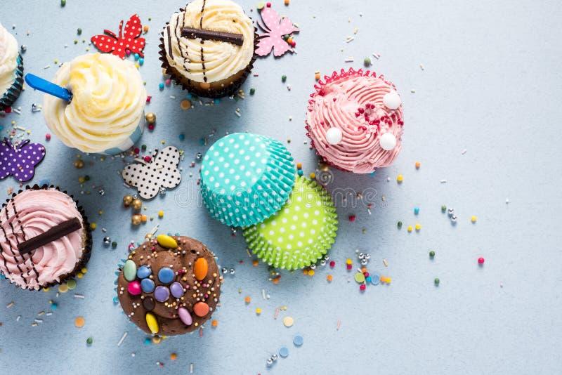 Vibrierende kleine Kuchen auf blauem Hintergrund, Parteilebensmittelkonzept stockfoto