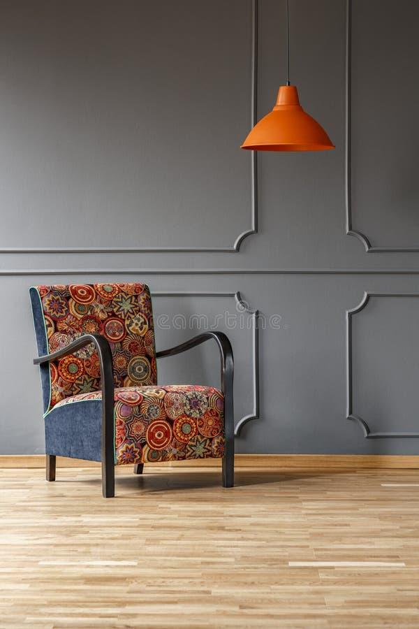 Vibrierende orange Deckenleuchte und ein bequemer Lehnsessel mit einem bunten boho Muster in einem grauen Wohnzimmerinnenraum mit lizenzfreie stockfotografie