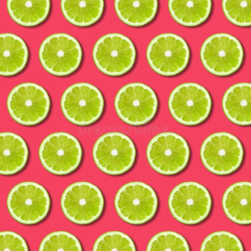 Vibrierender Fruchtpop-arten-Hintergrund mit grünen Kalkscheiben auf rotem Hintergrund stockbild