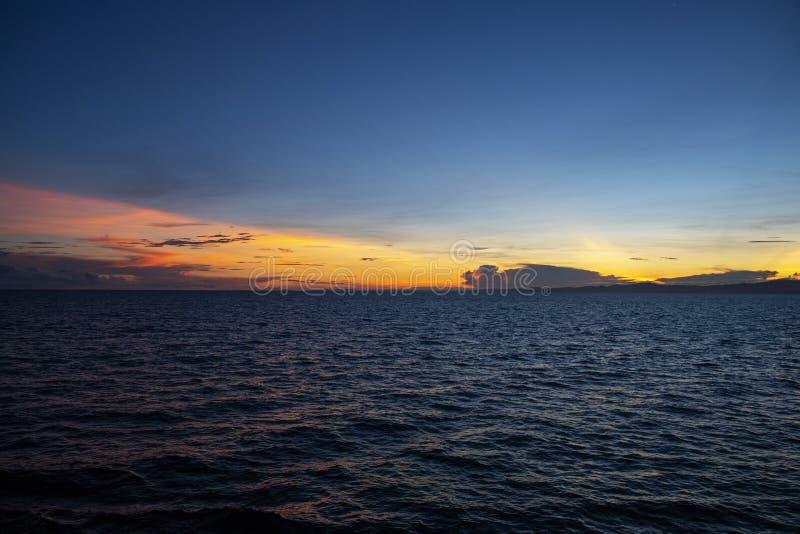 Vibrierender Sonnenaufgang mit blauem Himmel, orange Wolken und geplätschertem Meer Orange blaues skyscape am frühen Morgen lizenzfreies stockfoto