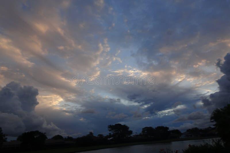 vibrierender und stürmischer Sonnenuntergang in den Tropen mit einem Schattenbild von a stockfotos
