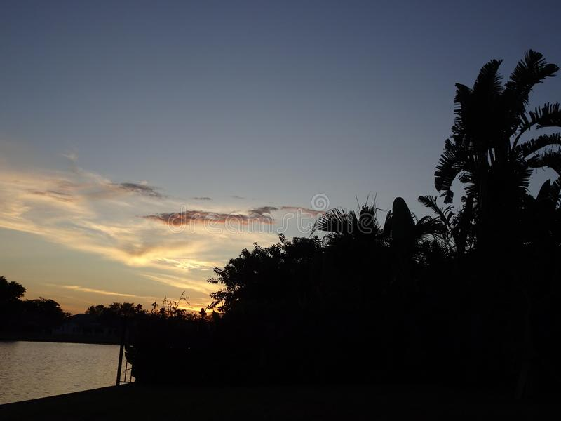 vibrierender und stürmischer Sonnenuntergang in den Tropen mit einem Schattenbild von a stockbild