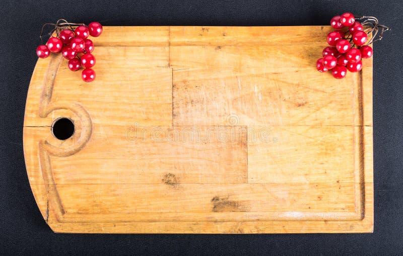Viburnumbeeren auf altem getragenem heraus Schneidebrett auf dem schwarzen Hintergrund Raum für Text Billet für Postkarte stockfotografie