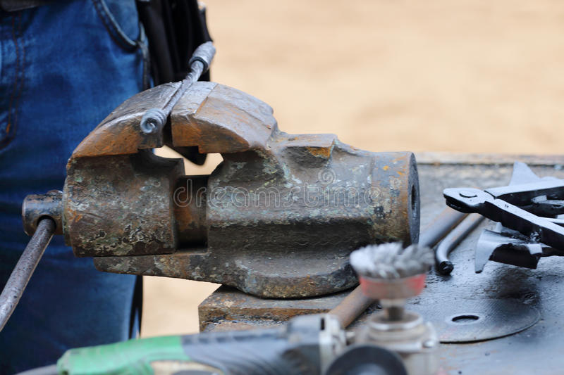 Vice with metal forged object, blacksmith tools and jeans stock image