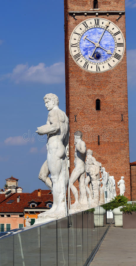 Vicenza, Italy. Ancient white stone statues of people over the B. Asilica Palladiana and the big clock tower stock image