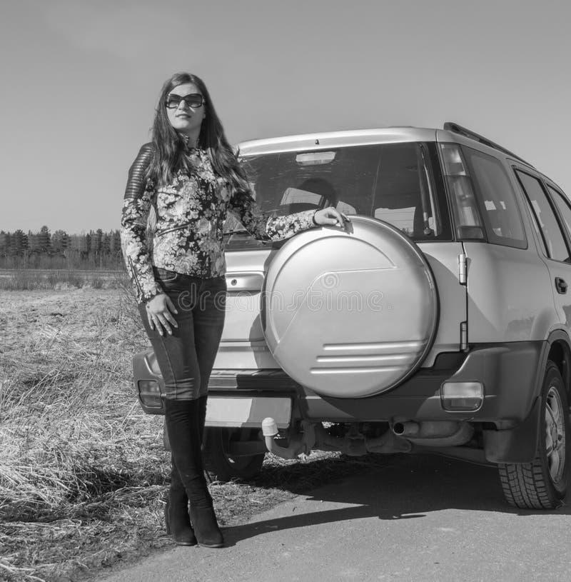 Vicino alla ruota di riserva l'automobile è bella ragazza, in bianco e nero immagini stock