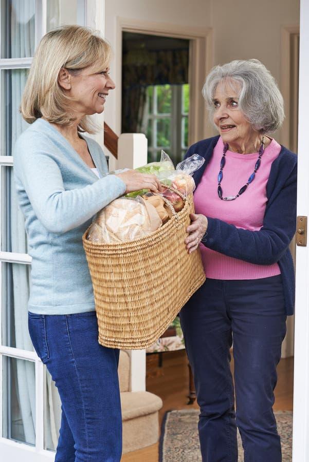 Vicino femminile che aiuta donna senior con acquisto fotografia stock libera da diritti