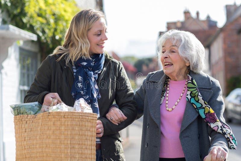 Vicino maturo che aiuta donna senior a Carry Shopping immagine stock libera da diritti