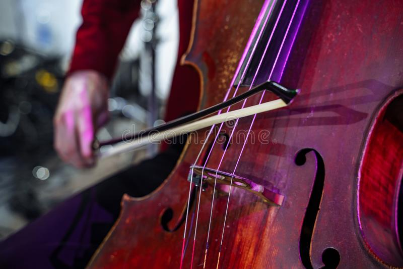 Vicino - su del violoncello dello strumento musicale Le mani degli uomini che giocano lo strumento fotografia stock libera da diritti