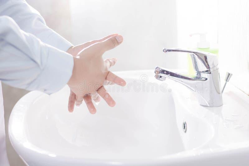 vicino su della mano bagnata di medico femminile che wasihing fra il dito nel lavandino bianco con il flusso continuo il sapone e fotografie stock libere da diritti