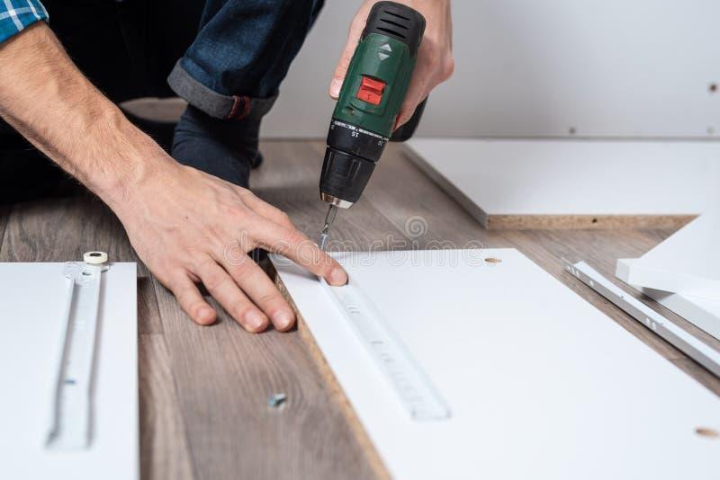 Vicino - su delle mani degli uomini raccolga la mobilia con le guide di torsione del cacciavite sullo scaffale fotografia stock