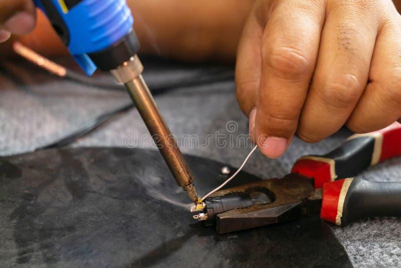 Vicino su di ingegneria di microelettronica Cavo di saldatura che ripara il cavo del microfono fotografia stock