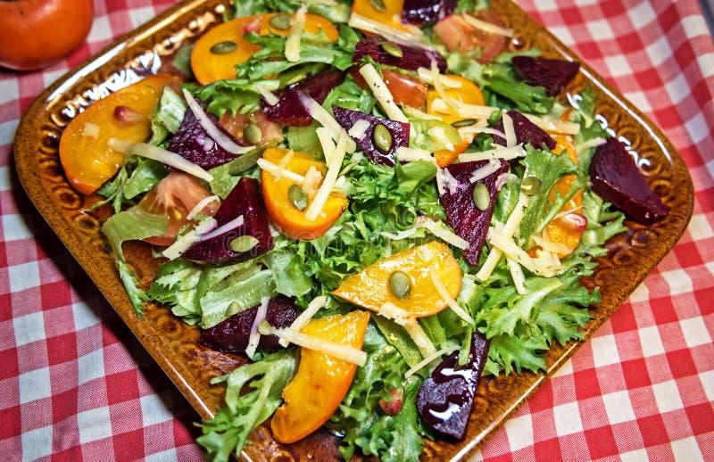 Vicino - su di un'insalata deliziosa di autunno con il cachi del cioccolato, lattuga, pomodori, melograno su un piatto dell'argil fotografie stock libere da diritti
