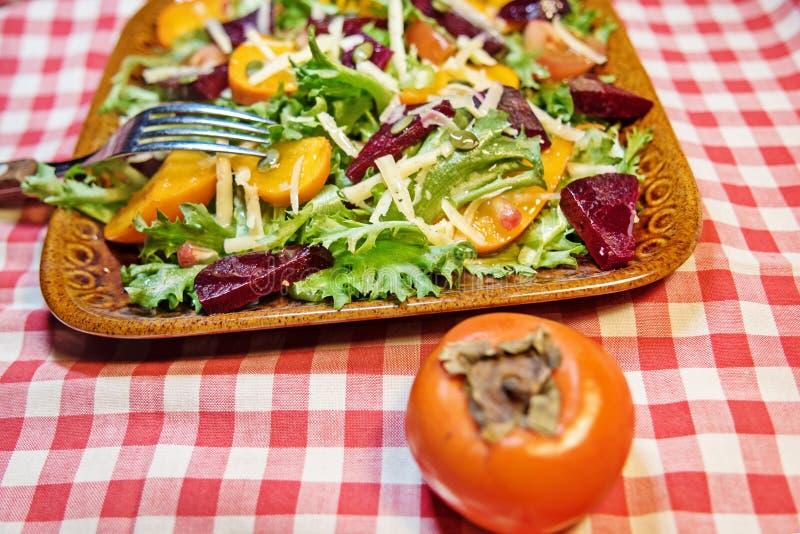 Vicino - su di un'insalata deliziosa di autunno con il cachi del cioccolato, lattuga, pomodori, melograno su un piatto dell'argil immagini stock