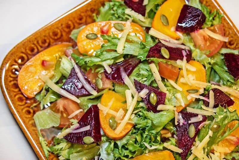 Vicino - su di un'insalata deliziosa di autunno con il cachi del cioccolato, lattuga, pomodori, melograno su un piatto dell'argil fotografia stock libera da diritti
