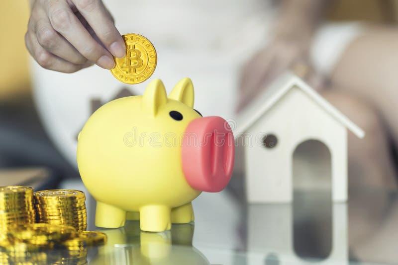 Vicino su, mano femminile che tiene bitcoin e che mette moneta nel porcellino salvadanaio giallo Conservi i concetti dei soldi fotografie stock