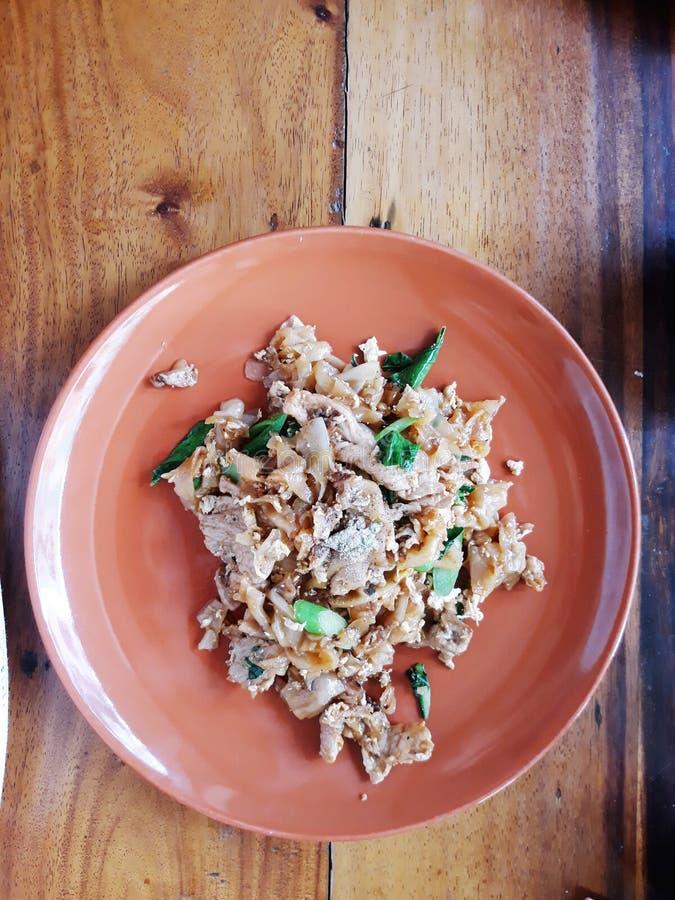 Vicino su mescoli la tagliatella e la carne di maiale piane fritte con la pasta conservata del fagiolo della soia fotografia stock libera da diritti