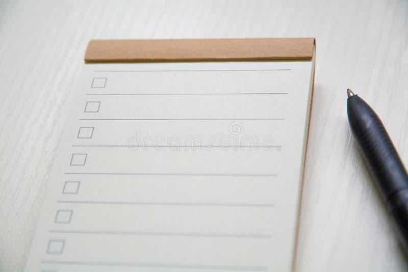 Vicino su? taccuino e penna della lista di controllo sul desktop fotografie stock