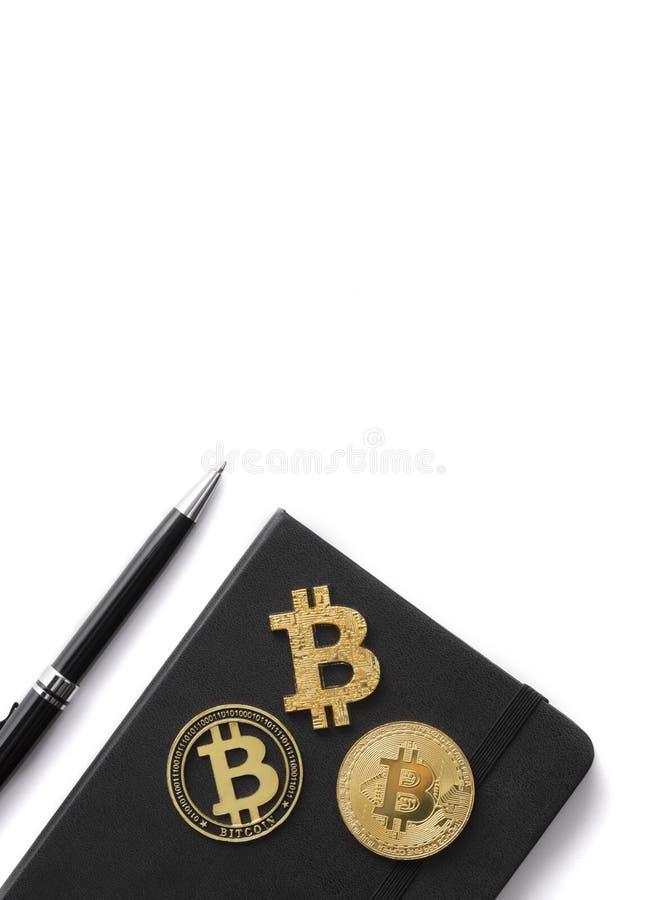 Vicino su tre monete, blocco note e penne del bitcoin isolati su bianco immagini stock libere da diritti