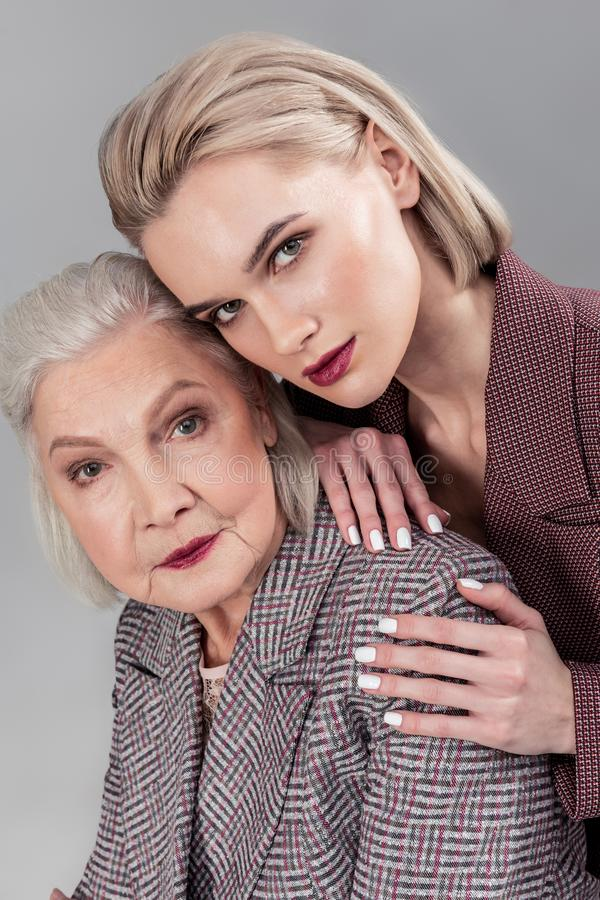 Vicious appealing ladies having short light hair and wearing jackets stock image
