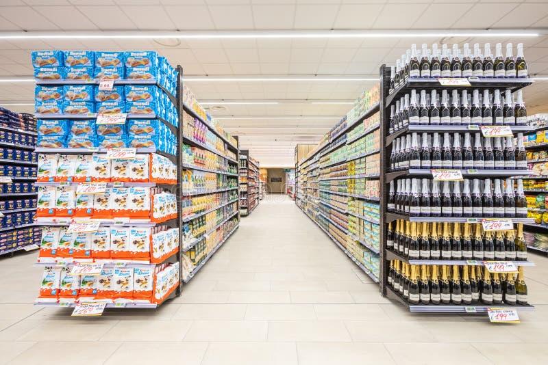 Vicoli degli scaffali con la navata laterale dei prodotti delle merci dentro un supermercato immagini stock