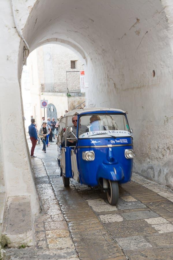 Vicoli di Ostuni Italia del ai del turisti del porta i del che del carruaje del mono fotos de archivo