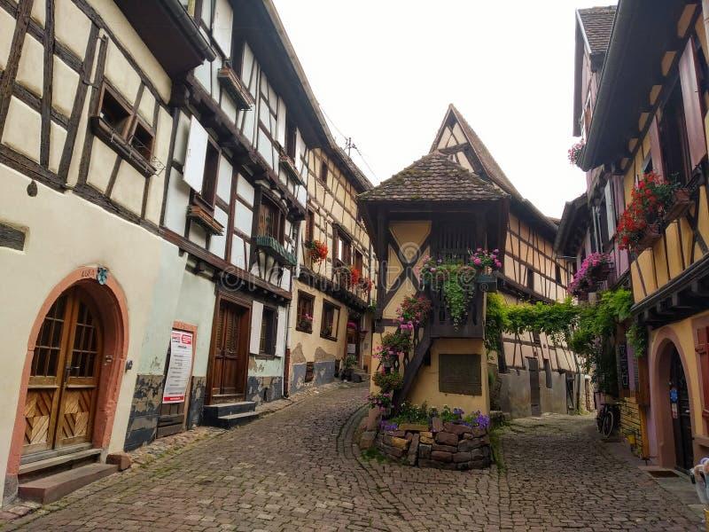 Vicoli pittoreschi di Eguisheim, vecchie case tipical decorate con i fiori, Francia immagine stock libera da diritti