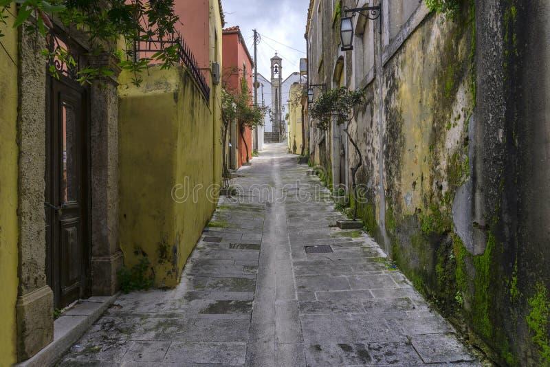 Vicolo pavimentato stretto, nel villaggio di Archanes che conduce ad una chiesa, con le vecchie case tradizionali fotografie stock libere da diritti
