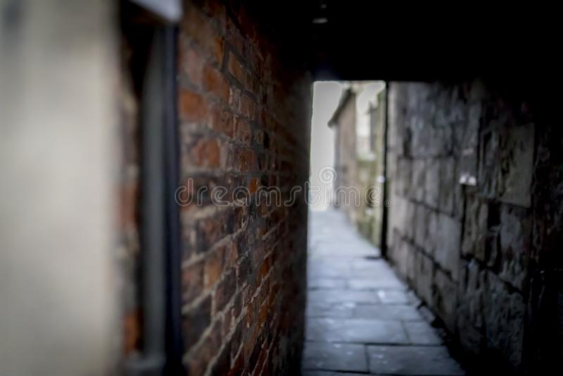 Vicolo scuro spettrale e terrificante del mattone o passaggio nascosto che conduce a fotografie stock